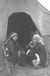 WOMEN SQUAT AT THE ENTRANCE OF THEIR TENT. THEY ARE NOT USED TO CHAIRS IN ADEN, YEMEN.
