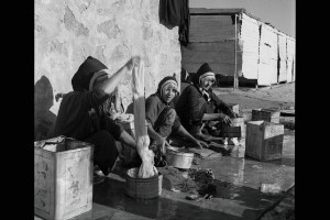 """PLENTIFUL WATER GIVES THESE YEMENITE WOMEN A CHANCE TO WASH THEIR SHEETS. AT THE BACK ARE THE LATRINES, AN INNOVATION FOR MOST OF THESE PEOPLE.""""HASHED CAMP"""", YEMEN."""