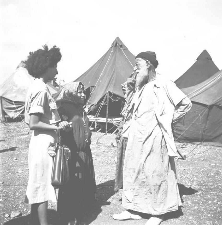 עולים מתימן במעברת ראש העין ב-1949, האישה המבוגרת (משמאל) מחזיקה בידה של הצעירה שלצידה.  מאחוריהם - האוהלים - מקום מגוריהם של העולים שלבושים בבגדים מסורתיים.
