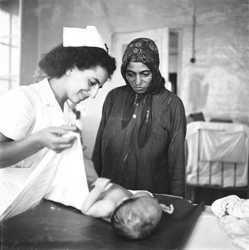 בית התינוקות במעברת ראש העין. משמאל אחות מטפלת בתינוק. אמו, מימין, לבושה בלבוש מסורתי מתבוננת בתינוקה